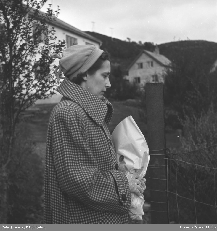 Høst i Rypefjord. Aase Jacobsen på besøk hos sine foreldre Arne og Sigrid Nakken. Hun har en rutet kåpe og lys lue på seg. I de hanskekledte hendene holder hun en innpakket blomsterbukett. En port til et nettinggjerde ses foran henne og et tre like bak. Nakkens hus ses litt diffust i bakgrunnen. Ved siden av står Ranveig Bergs hus. Noen el-stolper ses langs fjellkanten bak på bildet.