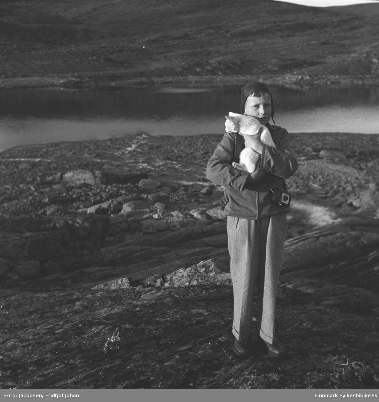 Arne Jacobsen poserer med en katt i armene. Han er iført en lys bukse, litt mørkere jakke og mørk/sort lue. Det er stort sett stein som dekker bakken der han står og et vann ses i bakgrunnen. En fjellside ses bak vannet.