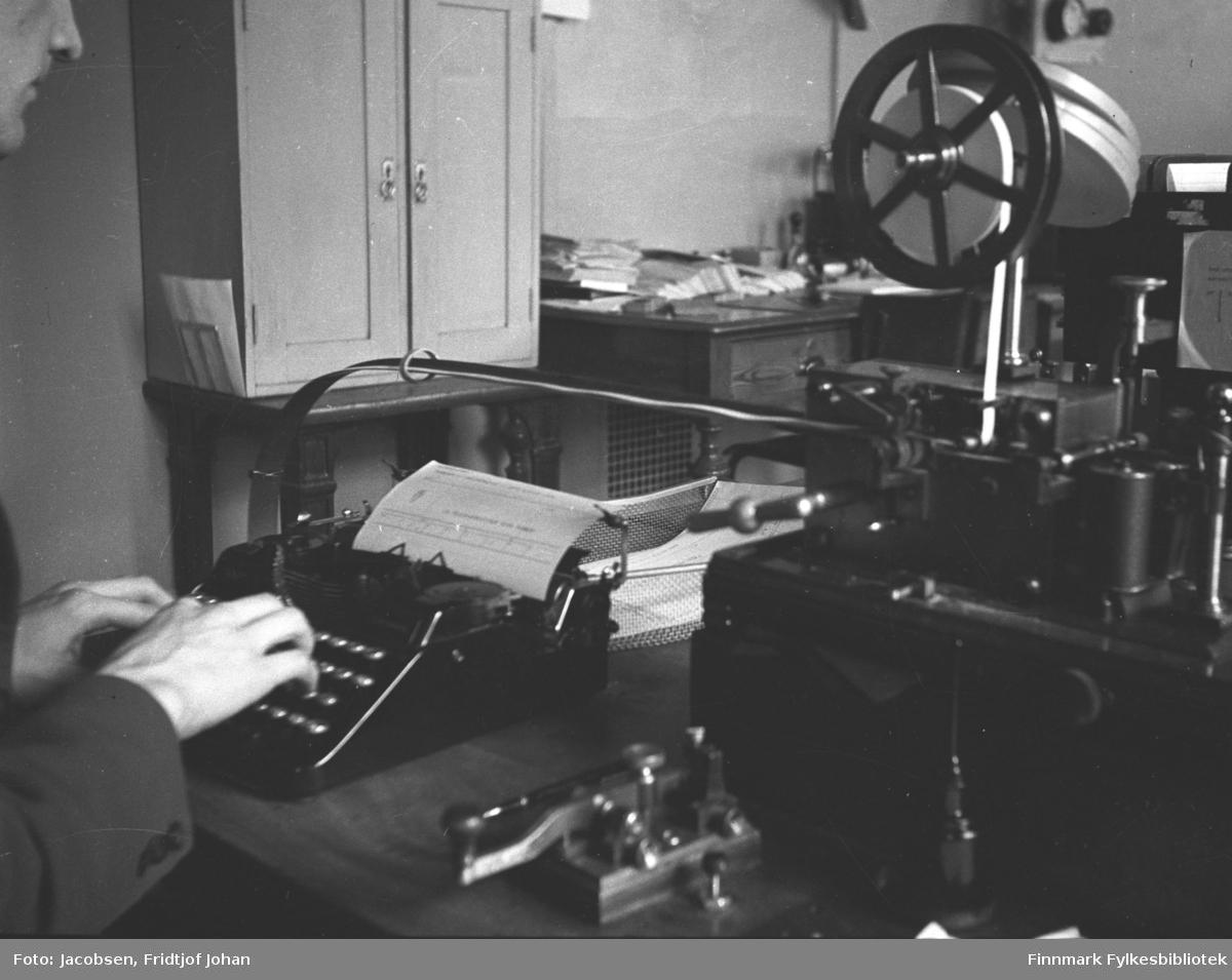 Telegramutskrivning på telegrafavdelingen ved Telegrafverket i Hammerfest. Mannen som skriver kan være Knut Ekrem. Et telegram står i maskinen han skriver på og en del utstyr/maskiner står på bordet foran han. Et skap med to dører står ved veggen til venstre på bildet. Ved siden av står et skrivebord med mye småting oppå.