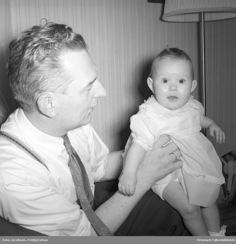 Ragnvald Jacobsen med datteren Ranveig, som her er ett år. Bildet er tatt i Corn. Moes gate 21, sannsynligvis 20. april. Rannveig har en lys kjole på seg. Rangvald har lys skjorte med mørkt slips og en mørk bukse med bukseseler over skuldrene. Deler av en stålampe ses i bakgrunnen.