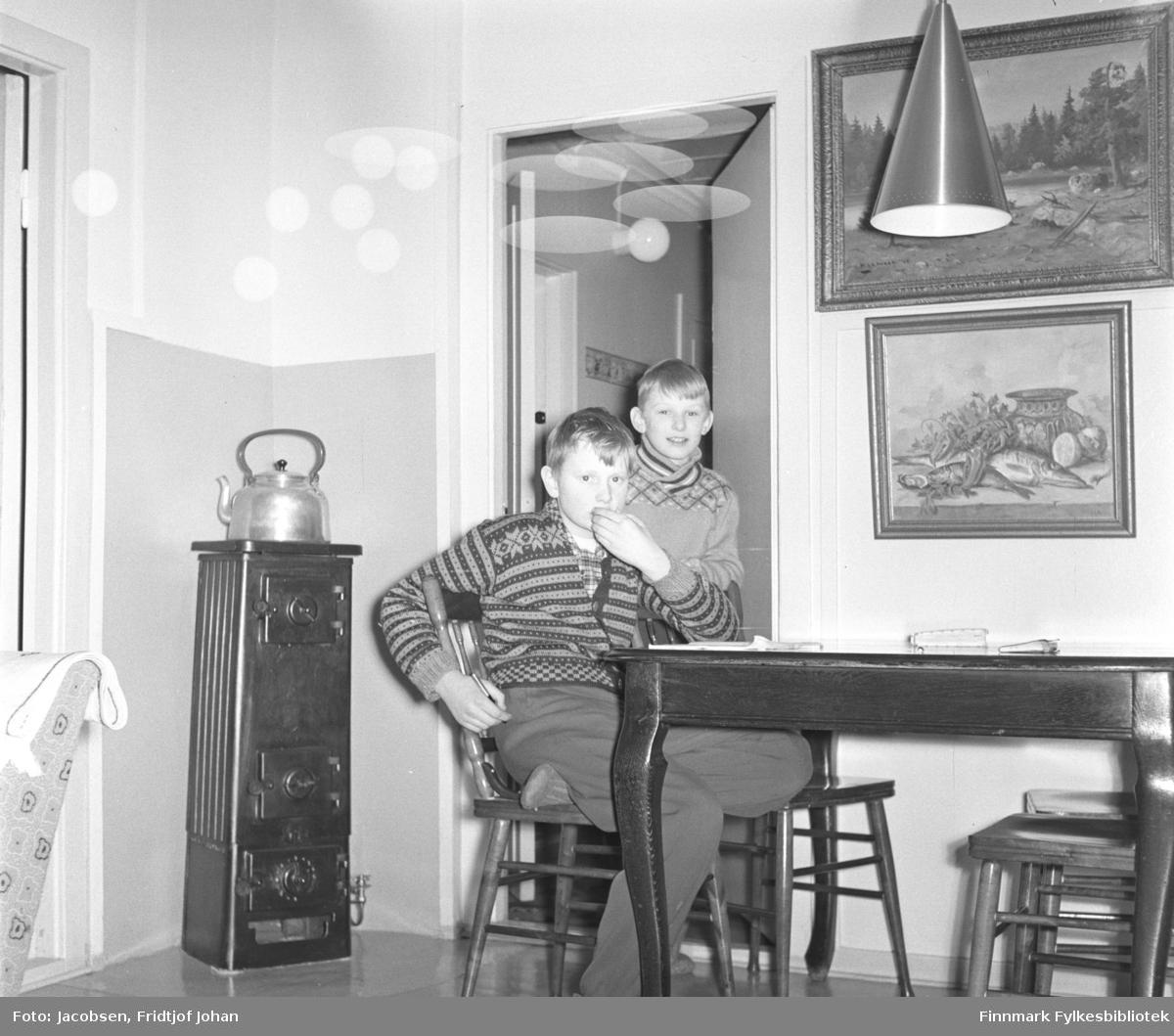 Fra stua til Fridtjof og Aase Jacobsen i Storvannsveien, vinteren 1958. På stolen sitter Arne Jacobsen. Han har en ganske lys bukse og strikkejakke med mønster på seg. Bak han står fetteren Ivar, iført en lys genser. Bordet og pinnestolene er mørke. To malerier henger på veggen over det og en taklampe ses oppe til høyre på bildet. En høy vedovn står i hjørnet med en stor kjele oppå.