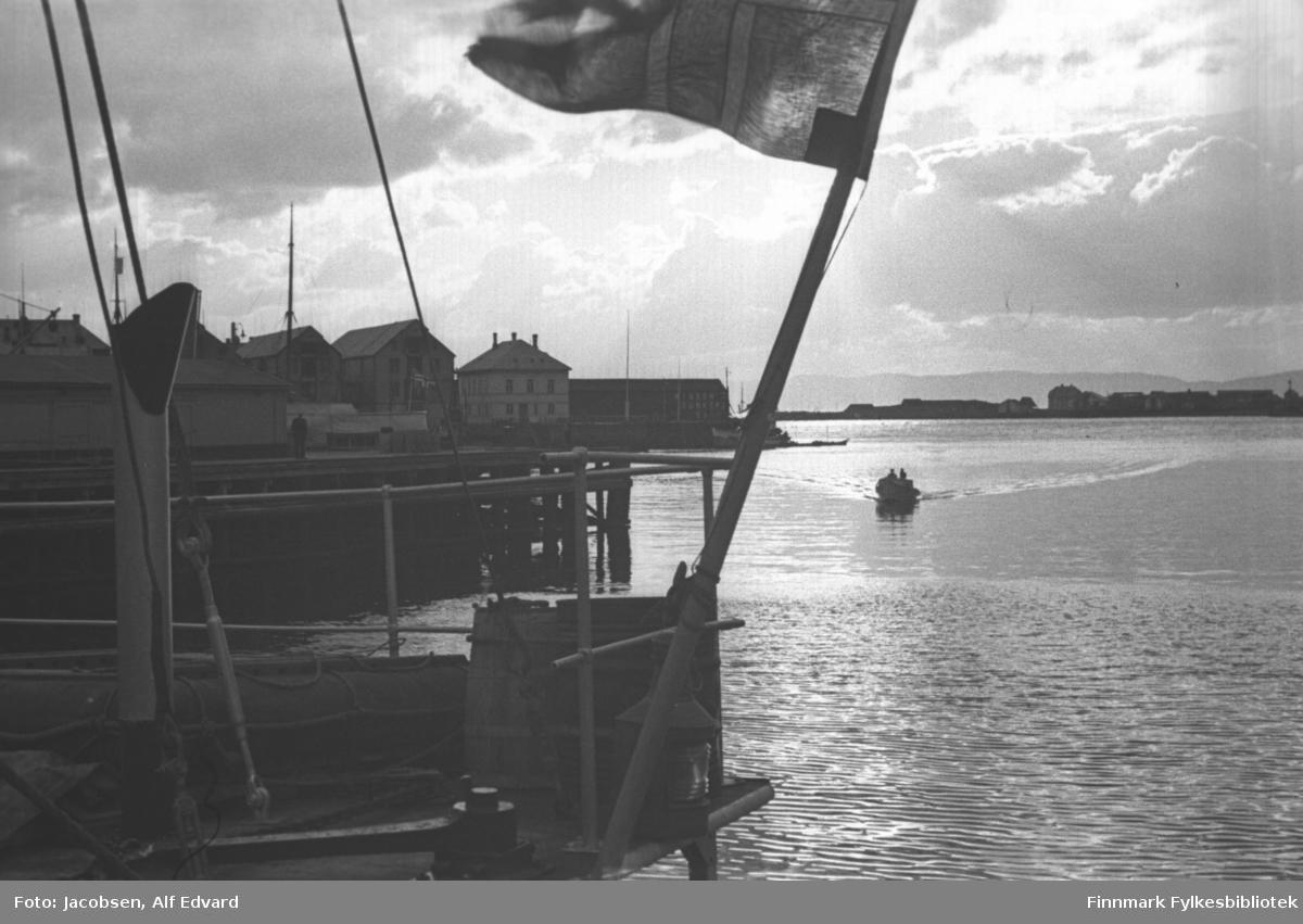 Bilde av havneområdet i Hammerfest tatt fra en båt. En flaggstang står på skrå ut fra hekken med det norske flagg i toppen. En lanterne er skrudd på rekkverket som er av metall og hvitlakkert. Et eksosrør stikker opp til venstre på bildet. Noen tau er festet til rekka. Kaia som stikker ut fra venstre på bildet er Dampskipskaia. I bakgrunnen, på Hammerfest-neset, ses flere store bygninger. Helt ute på neset står Nissens kull-lager. Til venstre for det ligger tollboden. Videre innover havna ligger flere store pakkhus, bl.a Nissen. En liten lettbåt er på vei inn havna. På andre siden ses Fuglenesodden bl.a med Robertsons kull-lager nesten ytterst. Noe diffust ses fjellene på Sørøya bak Fuglensodden. Små bølger på sjøen og sola som bryter gjennom skyene på himmelen får det til å se ut som en fin sommerdag.