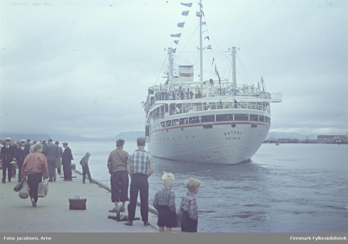 Turistskipet Batory ved dampskipskaia i Hammerfest. Skipet har mange flagg/vimpler og mange av passasjerene står på dekk. Landgangen henger ned langs skipssiden. Til høyre for skipet ser vi Fuglenesodden med sykehusbrakka. På kaia står mange mennesker. To av dem iført uniform med marineluer. To små gutter, nærmest kamera, med kortbukser og skjorte/genser med lange ermer. En veske står midt på kaia og en dame, med ryggen til, bærer på mye bagasje. I horisonten ses Sørøya innhyllet i tåke/dis.