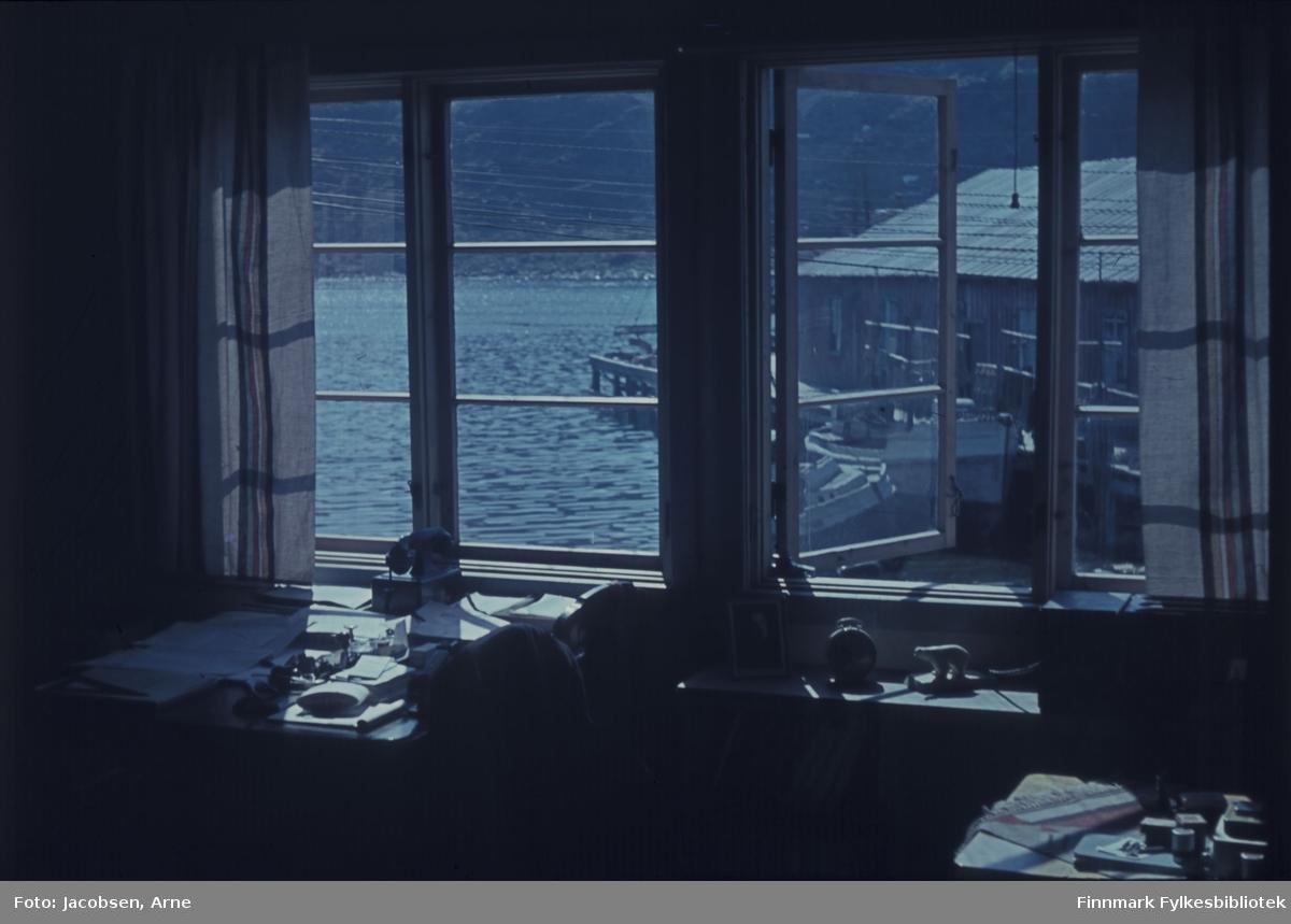 Fra Fridtjof Jacobsens kontor. Til venstre står skrivebordet med noen papirer, en telefon og litt skrivesaker. Ved siden av, en hylle med et bilde, en klokke og en liten isbjørnskulptur. Helt til høyre et mindre bord som har en duk med frynser. Div. småtterier ligger oppå bordet. To todelte vinduer i bakgrunnen, hvorav en del er åpent. Utenfor ses en kai med et pakkhus og noen båter ligger ved kaia. Mye ledninger går på tvers og ses langs hele vinduet. Ute skinner sola og det er ganske stille på sjøen. Et fjell ligger på andre siden av sjøen, der man også ser fjæra.
