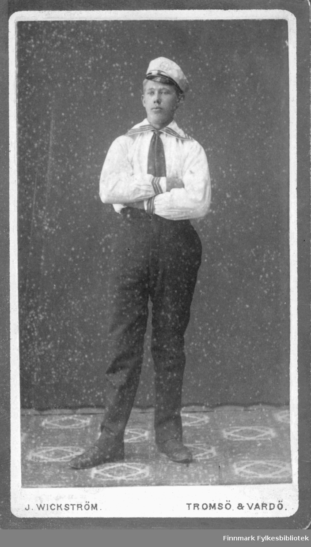 Portrett av ukjent ung mann. Han er kledt i en mørk bukse og hvit skjorte. Det ligner på en matrosdrakt. På kraven og mansjettene er det striper. I halsen har han et mørkt slips. På hodet har han en lue med skjerm