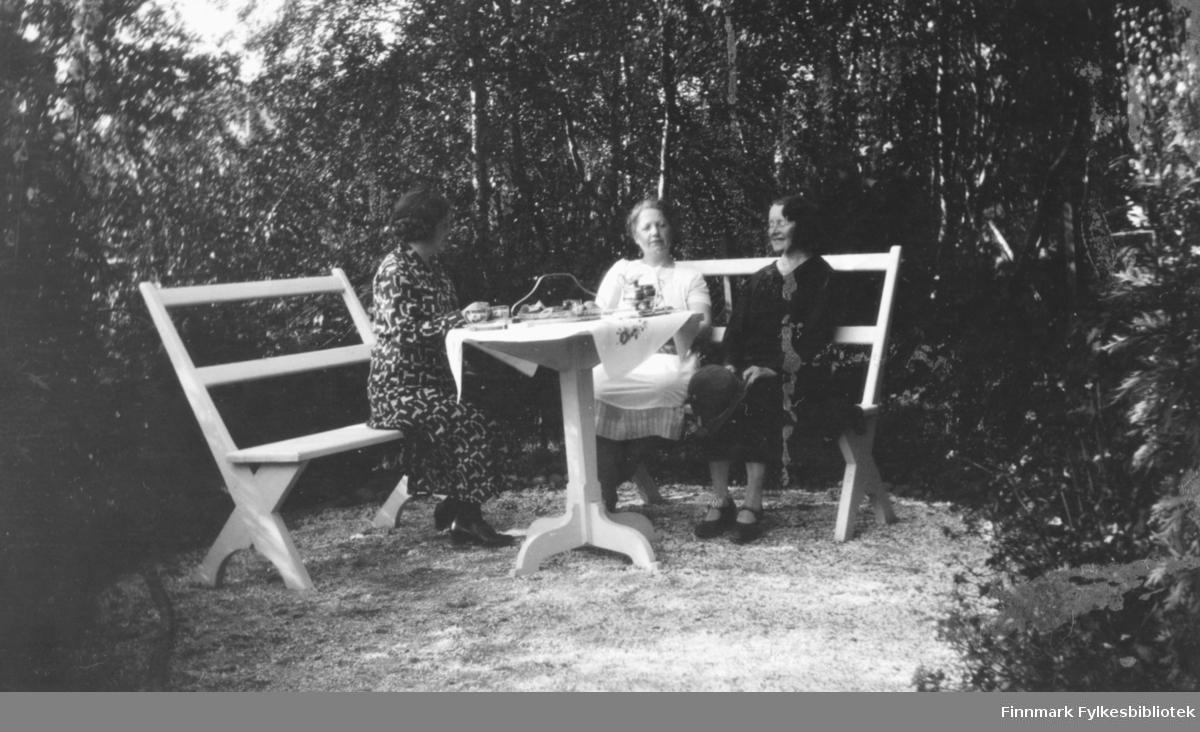 Bilde av tre kvinner som sitter ute på hvite trebenker rundt et hvitt trebord. Kvinnen til høyre i mørk kjole er lærerinne Julie Jacobsen fra Vardø. Bordet har duk og er dekket med kopper og en kanne. Midt på bordet står et kakefat. Rundt området kvinnene sitter er det tett med trær
