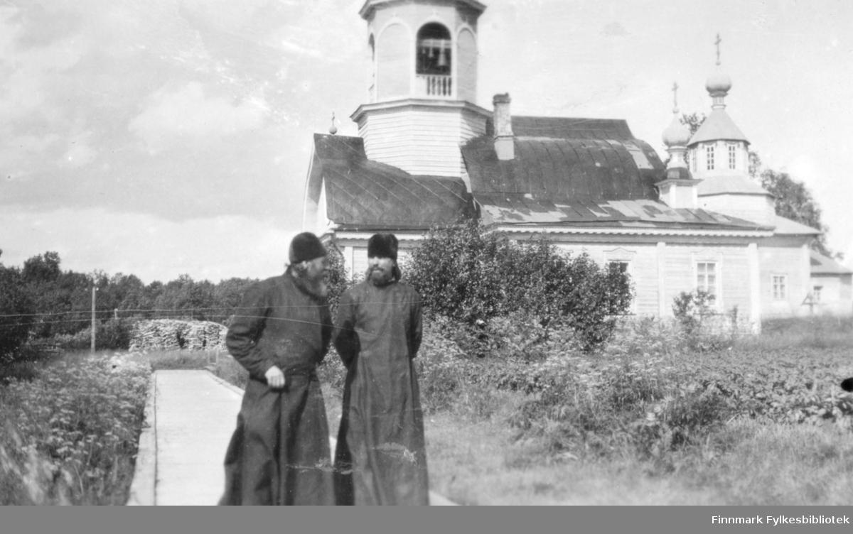 Fotografi av to munker med skjegg foran Tempelkirken i Petsamo i Russland. Begge munkene er kledt i munkekjortler og høye mørke luer. Den lyse trebygningen har bla. klokketårn, kupler og spir. Området rundt kirken er frodig med busker og trær