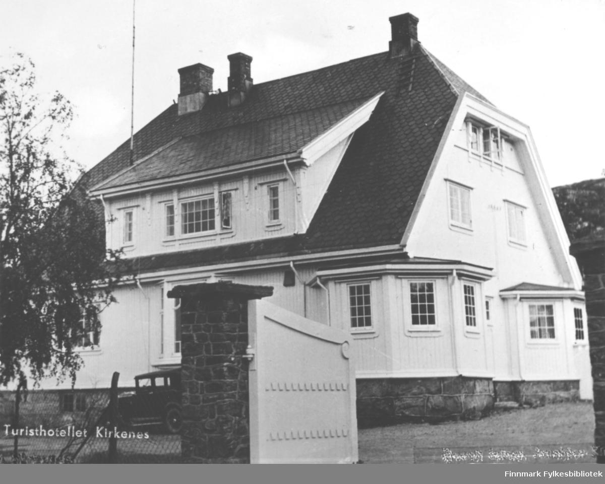 Postkort fra Turisthotellet i Kirkenes. Vi ser på bildet en stor hvit trebygning bygd i flere etasjer. Bygd på en mur. Det står en bil parkert utenfor. Det er nettinggjerde rundt huset. På hver side av den hvite treporten er det mursøyler