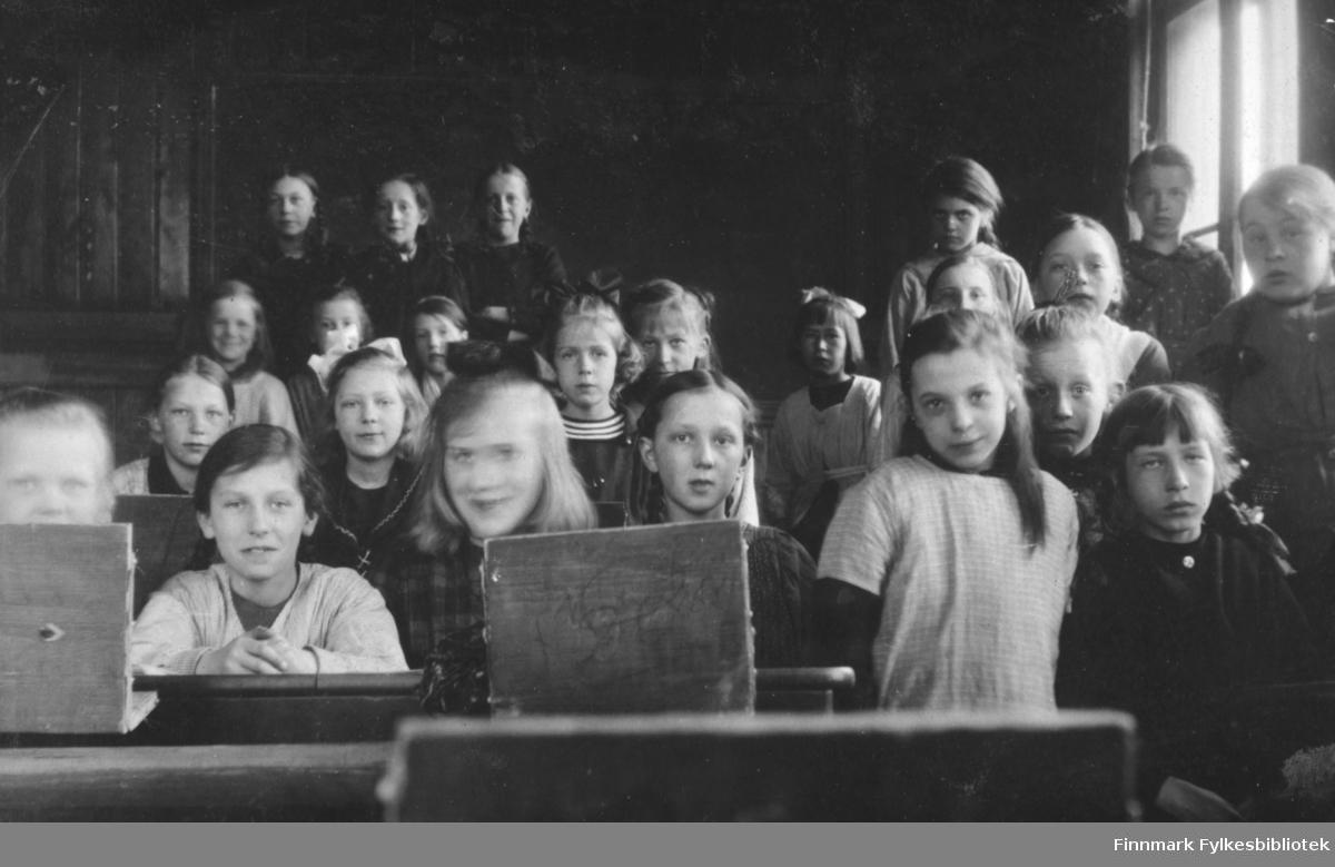 Fotografi av en skoleklasse  fra Vardø. Dette var en klasse som lærerinne Julie Jacobsen fra Vardø hadde. På bildet ser vi bare jenter. Noen sitter og noen står ved pultene. Bakerst i rommet står det tre mørkkledte kvinner