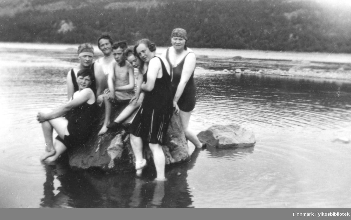 Fotografi av fire ukjente kvinner og tre gutter? som er kledt i badeklær. To av kvinnene har badeluer på. På bildet står og sitter de samlet på en stor stein uti et vann. I bakgrunnen er det fjell bevokst med trær