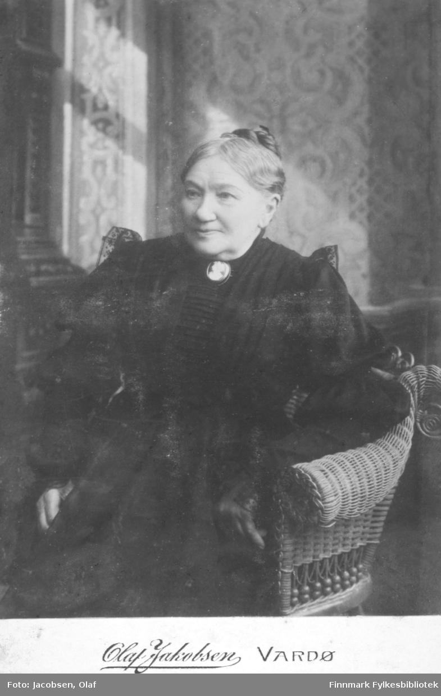 Portrett av ei ukjent kvinne som sitter i en rottingstol. Hun er kledt i en mørk kjole. I halsen har hun en kamebrosje. Håret er satt opp i en knute