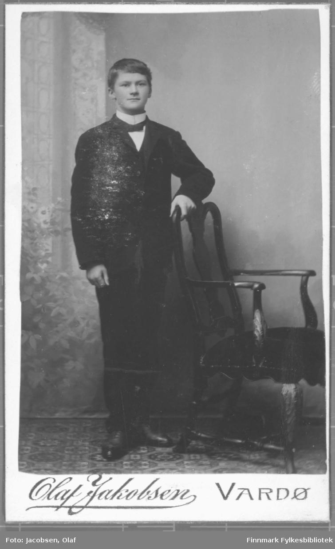 Portrett av en ung menn kledd i en mørk dress sløyfe og hvit skjorte med høy krage. studio ateliere malt bakgrunn holder hånd på stolrygg.  Albumet med bildet kommer fra Ekkerøy, kanskje han kommer derfra.