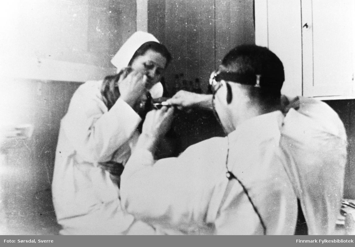 Overlege Sverre Sørsdal og oversøster Marthe Eckmann trekker en tann på en pasient. Martha Eckmann holder hodet støtt men Sverre Sørsdal trekker. Bildet er tatt i 1934-35.
