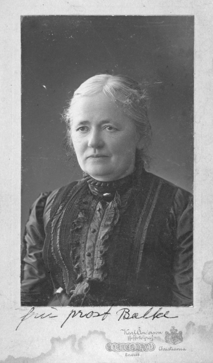 Påskrift på bildet: 'fru prost Balke'. Dette henviser trolig til Thora Balke som var kone av prost Georg Balke. Hun har på seg en kjole. Bildet trolig tatt på slutten av 1800-tallet, begynnelsen av 1900-tallet.