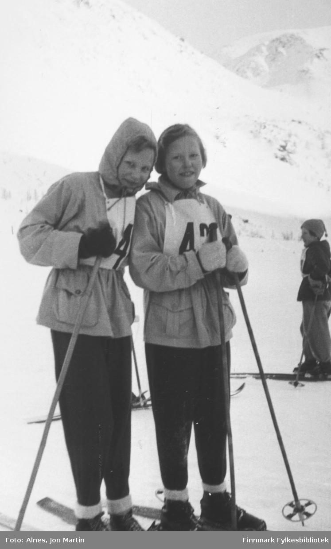 To blide deltakere på Øksfjord barneskoles skirenn i Vassdalen, 1953. Fra venstre: Nan og Erna Kiil. I bakgrunnen Hildegunn Hansen