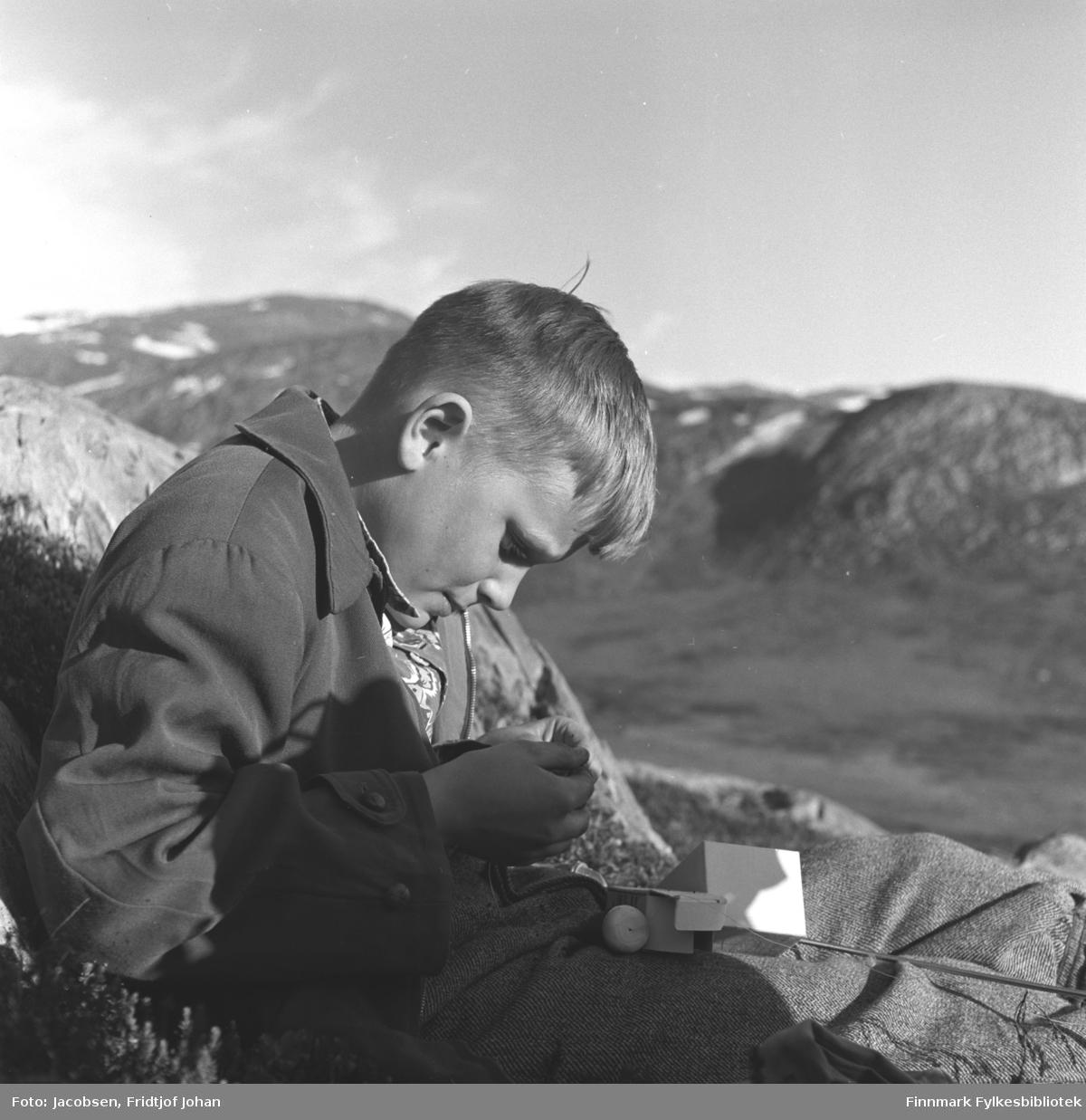 Arne Jacobsen sitter i terrenget og holder på med fiskestanga. Stedet er ukjent.