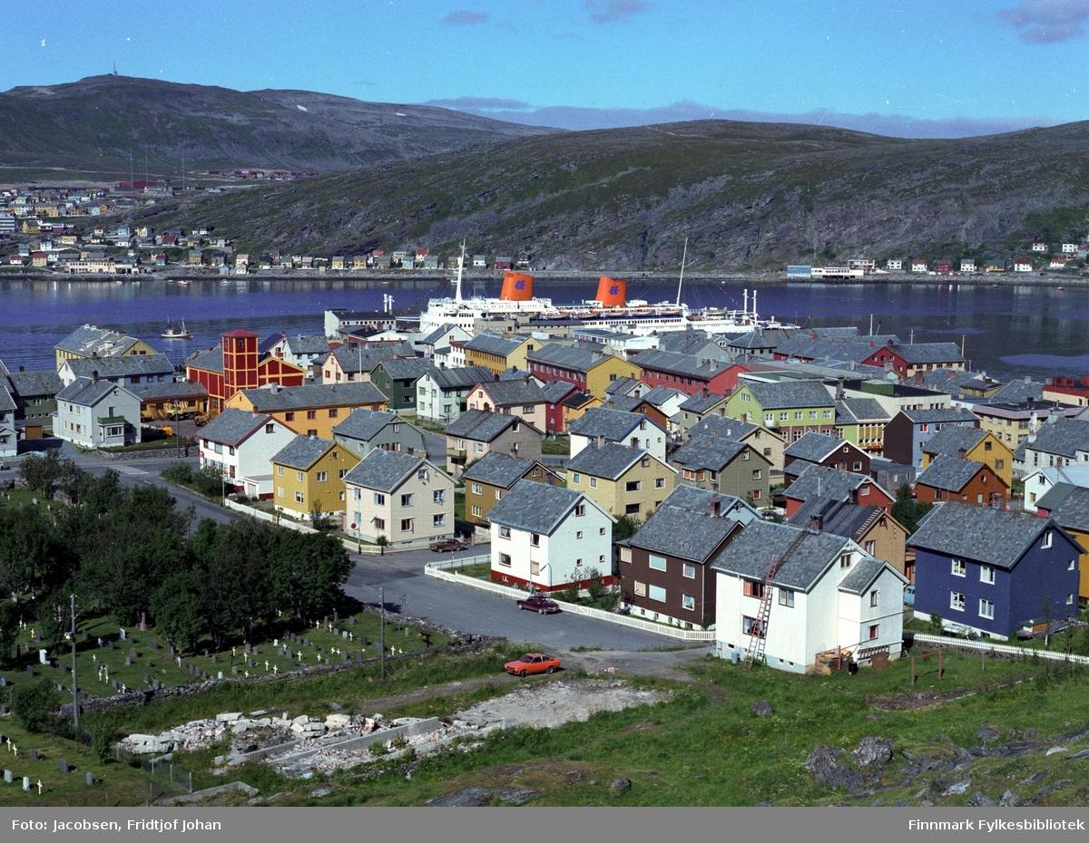 Motiv fra Hammerfest en sommerdag. Bydelen Fuglenes ses på andre siden av havna med Storfjellet bak. Fotografiet er tatt fra Salsiden.