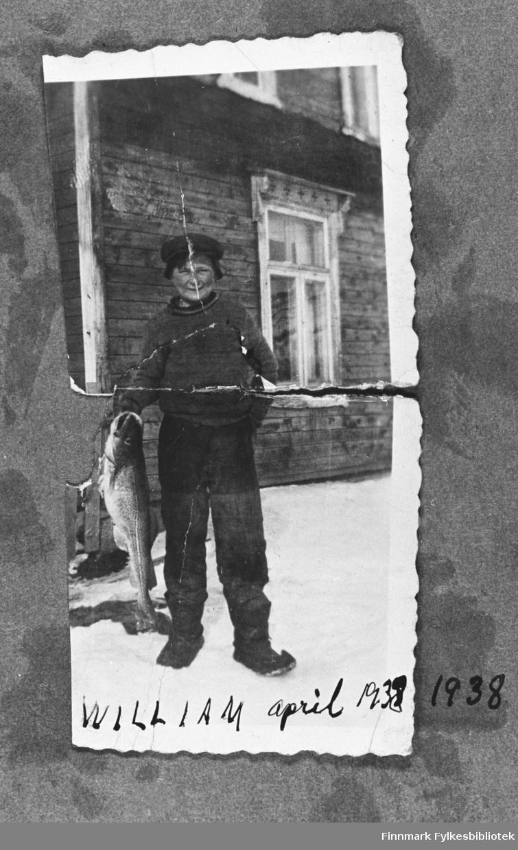 Ung gutt, William Mietinen, fotografert utenfor familiens hus i Vestre Jakobselv. Gutten har hjemmesydde kommager på seg og han holder en stor torsk på handen. På bakgrunn står husveggen med et vindu.