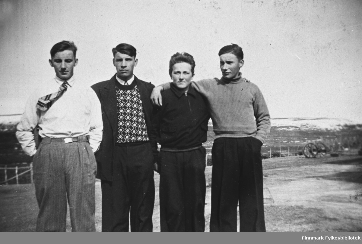 Fire stramme karer står på en veg i Karjel(?), mennene fra venstre Bjarne Wickstrøm, Isak Wickstrøm, Jakob Mietinen og Alf Wickstrøm. Det er byggdt gjerde langs vegkanten, langt bak ved vegkanten står det en kjærre. Bjarne har slips på seg, guttene er pent kledd.