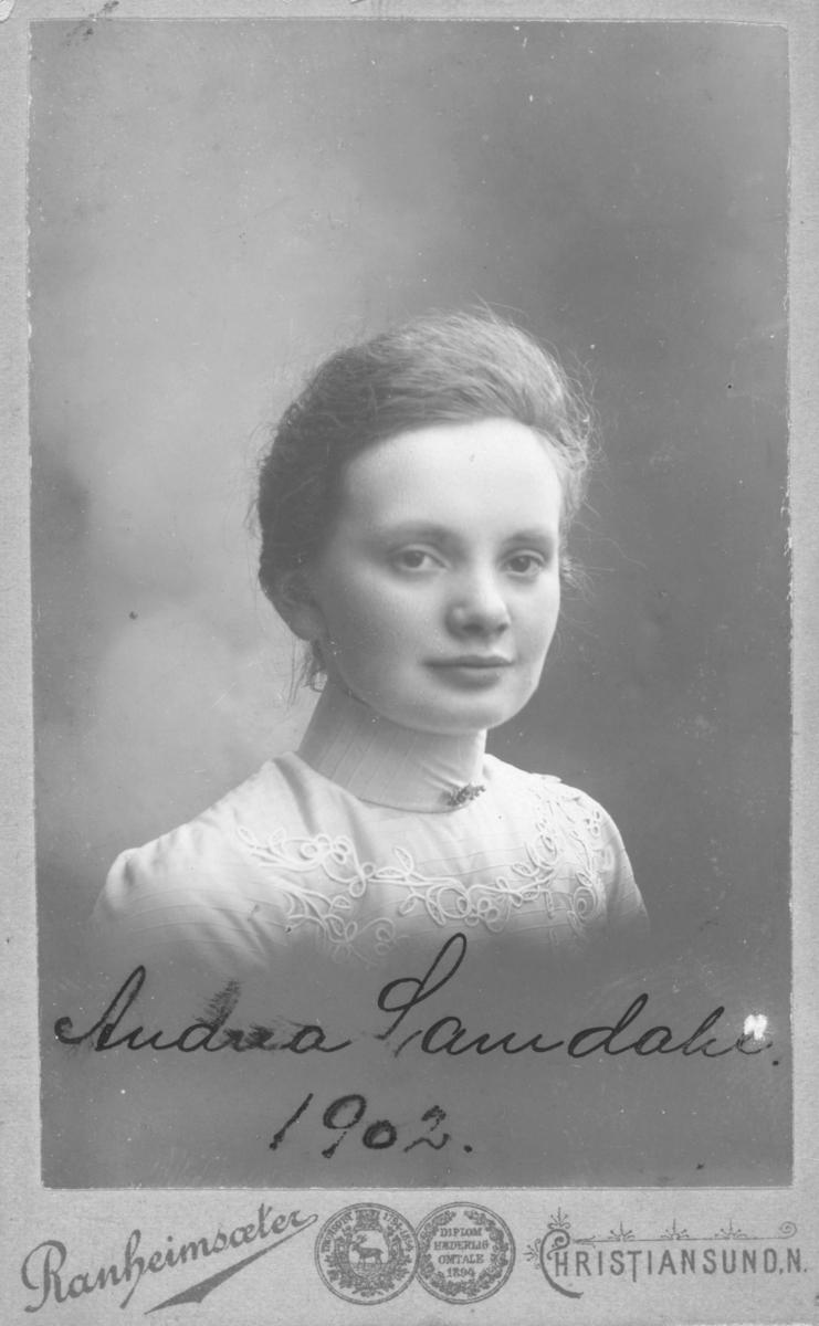 """Portrett av en ung kvinne, på bildet står det skrevet """"Andrea Samdahl, 1902"""". Andrea er iflg. Digitalarkivet født i Kristiansund kjøpstad og har som yrke """"Husgjerning""""."""