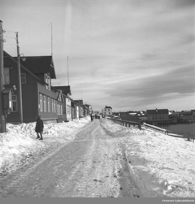 Fotografi fra Vadsø. Havnegata mot øst.  Til venstre i bildet går lærer Megrund. Bak ham sees Johannes Helfjords hus. I enden av gata skimtes Evangergården. Bildet er tatt før krigen. Fotograf ukjent.