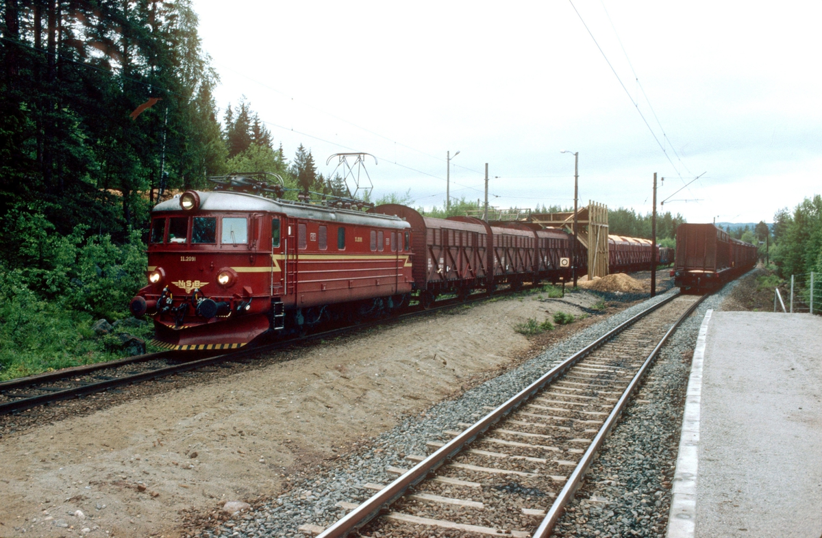"NSB godstog 5165 (Alnabru - Roa) skifter på Lunner almenning sidespor, ""Pipern"", ved Furumo (Harestua). Elektrisk lokomotiv El 11 2094. Her ble det lastet flis i flisvogner."