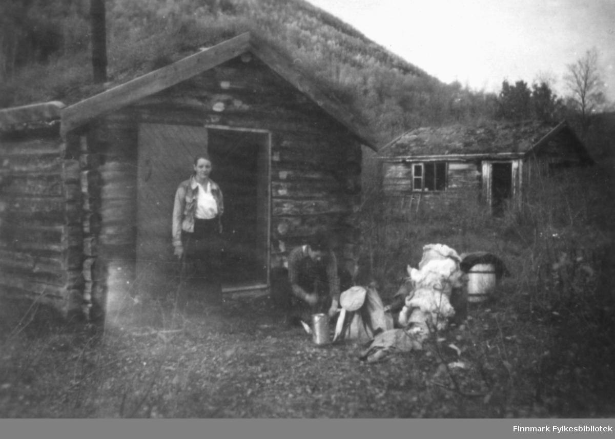 Magna Wisløff og et annet menneske foran en steinberghytte. Til høyre ser vi en lik hytte. Typiske hytter for steinbergsarbeidere i Alta. Foran ser vi reinskinn, tønne, spann og ryggsekk.