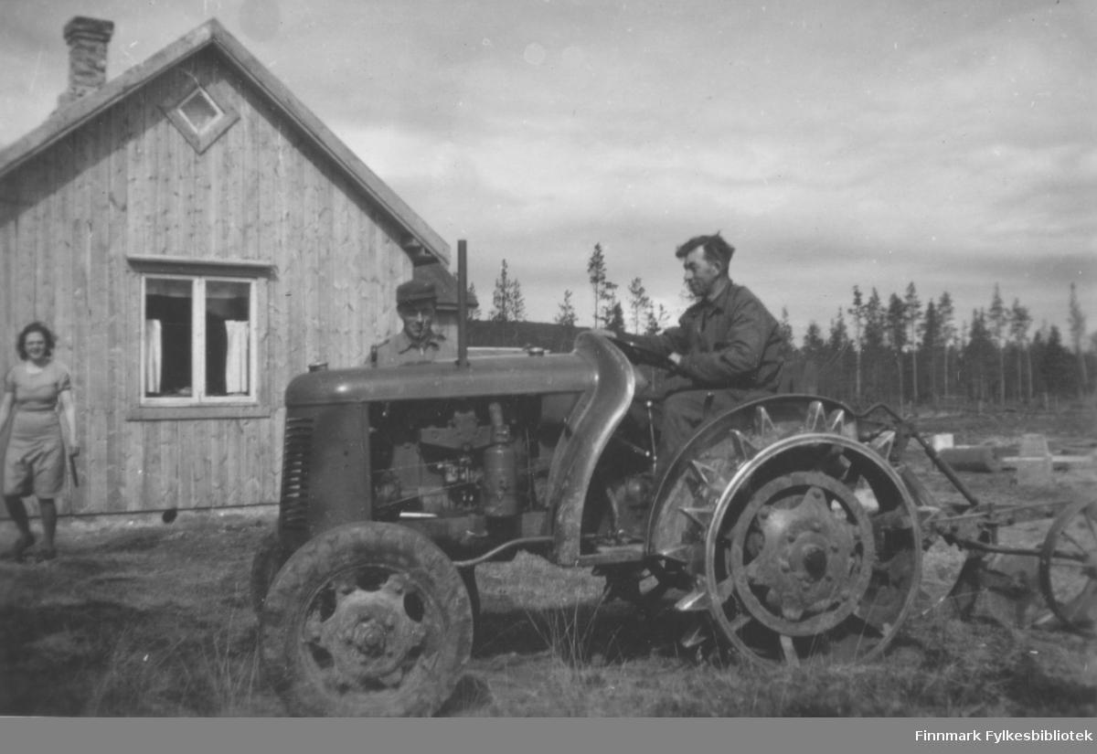 Kristian Wisløff sittende på en David Brown-traktor med en plog festet til. Wisløff pløyde opp adskillige mengder jord for folk i Altaområdet tidlig på 50-tallet. Vi ser en kvinne gående til venstre i bildet og en mann stående bak traktoren. Umalt bolighus. Rundt ser vi udyrka mark og i bakgrunnen furuskog