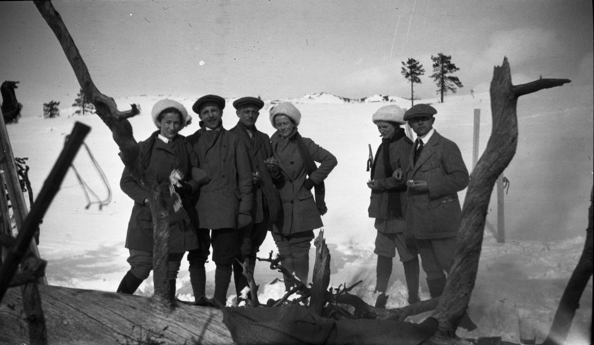 Fotoarkivet etter Gunnar Knudsen. Mennesker på skitur på fjellet.  Her har de tatt seg en matpause.