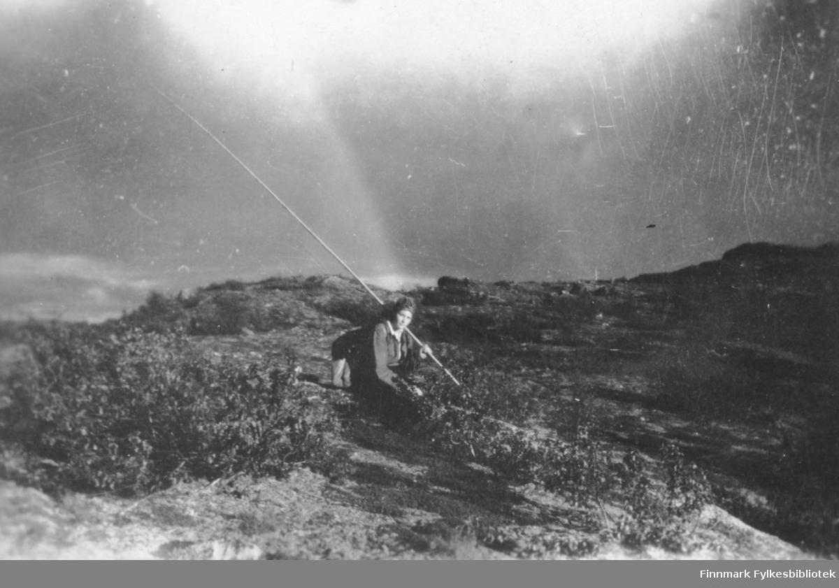 Beskades, Finnmarksvidda. Vi ser en kvinne sittende på lyngen med sekk på ryggen og fiskestang i hånda. Rundt ser vi viddelandskap og lav vegetasjon. ca.1950 tallet.