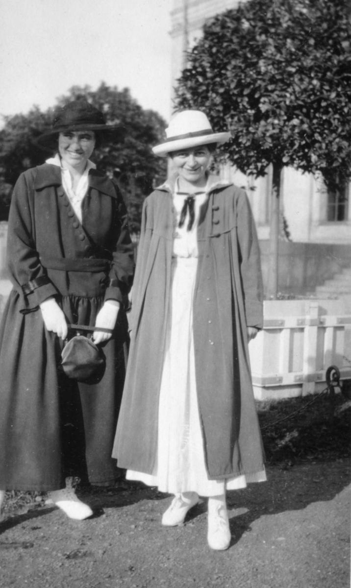 To ukjente kvinner poserer for kameraet. De har begge på seg kåper, hatter, sko og kjoler. kvinnen til venstre holder på en veske og har hansker på. De står på en grusvei og i bakgrunnen kan man se et gjerde, trær og en bygning med vindu og trapp. Bak damene kan man se et mindre gjerde med kjetting.