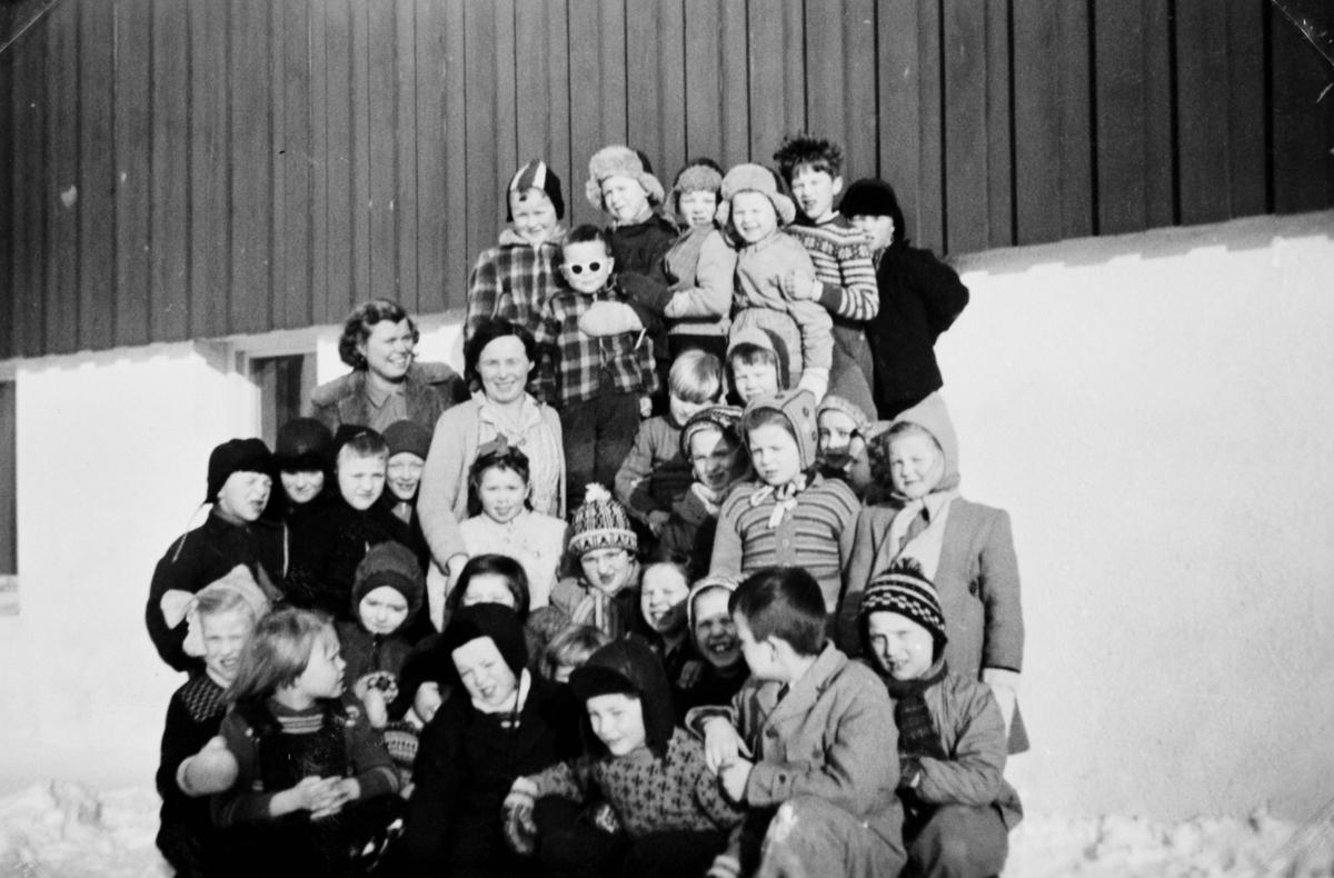 Gruppebilde av 1. og 2. klasse i Seida skole i 1955. Barn står foran skoleveggen i en fin vinterdag. En del av jentene har kledd seg i genserer, de fleste av guttene har på seg en jakke. Nesten alle har en lue på seg. To lærerinner står med elevene. Vi vet ikke navn til elevene eller lærerinnene.