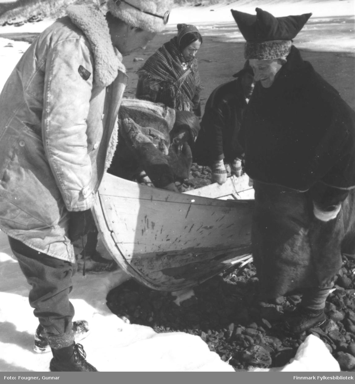 Samer og en politisoldat med elvebåt etter en båttur på Tana- elva. Samene i kofter og en i pesk. Soldaten har på seg saue- skinnsjakke.