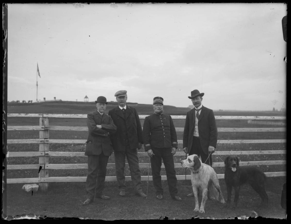 Foran Vardøhus festning. Kommendanten er enten Arnesen eller Holter. Mannen med hundene er muligens sakfører Håkon Evjenth.