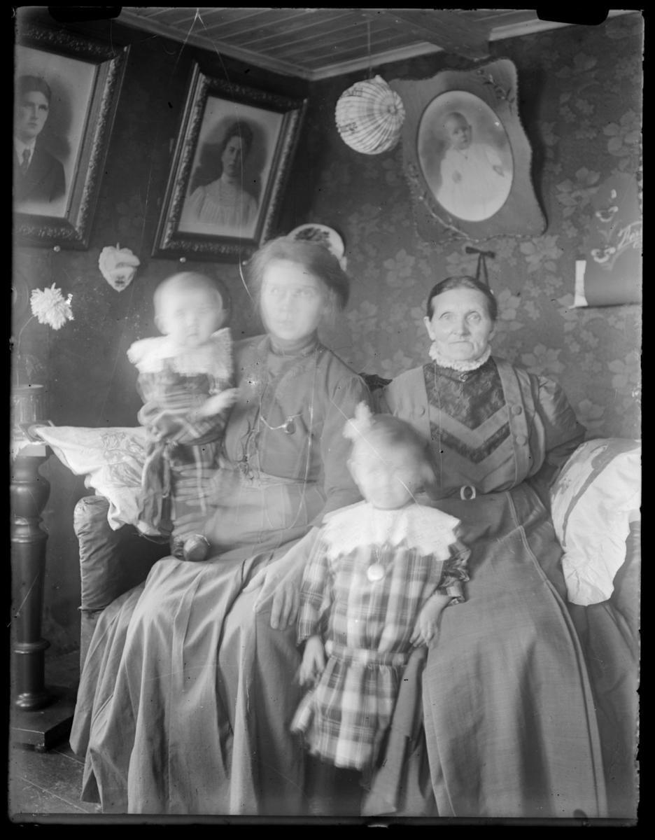 To ukjente kvinner og to barn fotografert i en svært lavloftet stue. Stua er vakkert tapetsert, og på veggene henger portretter, i taket en kinesisk lykt. Ved siden av sofaen kvinnene sitter på står en pidestall med blomster