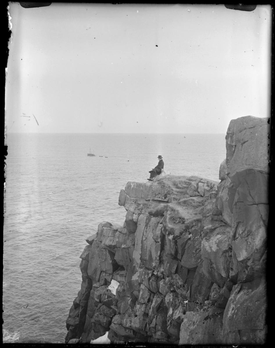 Mann sitter yttesrt i et klippeutspring med utsikt over havet. En båt med to lettbåter ligger fortøyd et stykke utpå