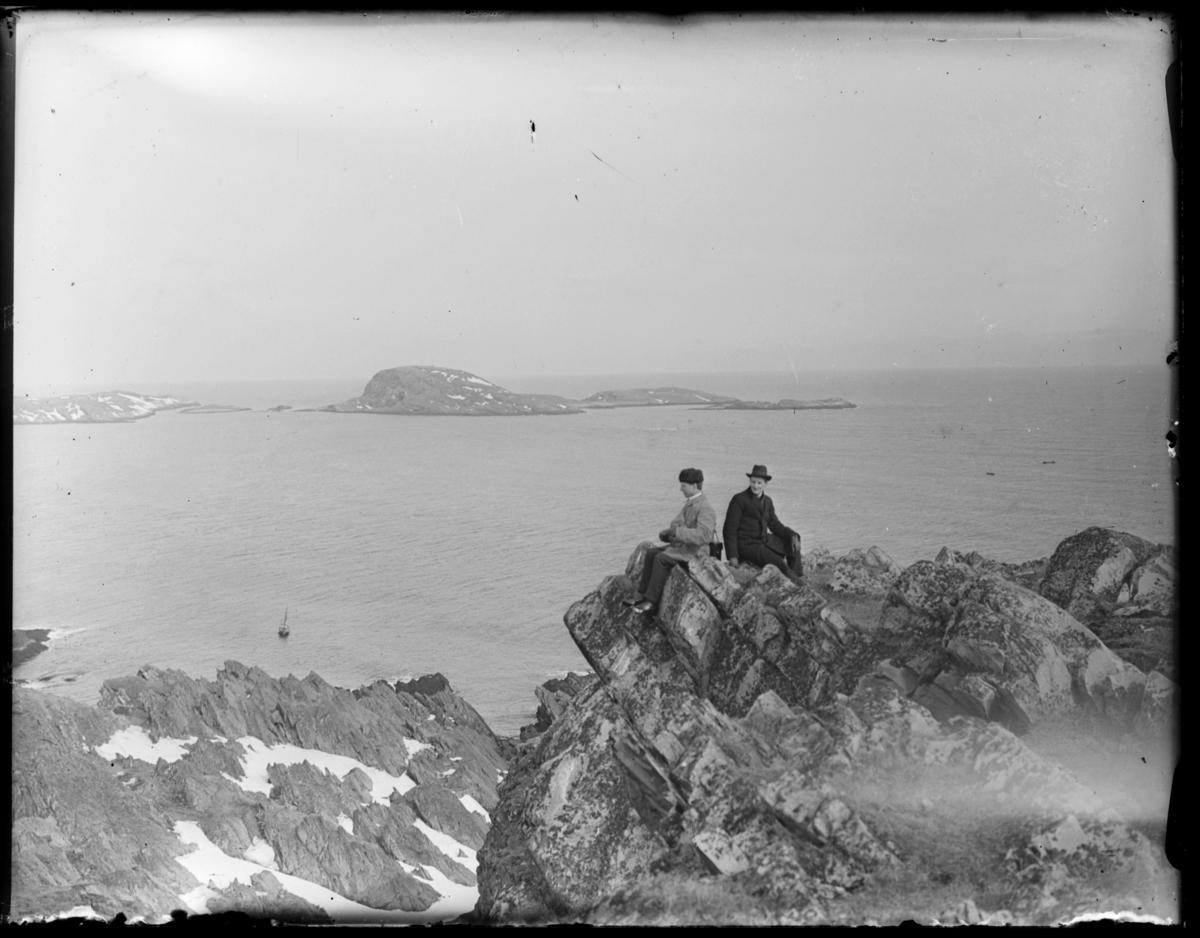 To menn sitter i et klippeframspring på Rødmoen med utsikt over havet og Reinøya og Hornøya. En seilbåt ligger fortøyd nedenfor klippeutspringet