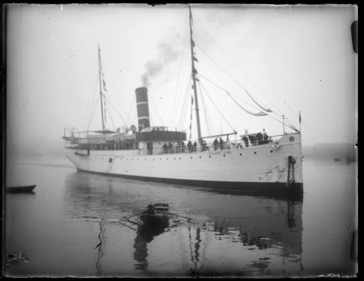 Hurtigruta 'Sigurd Jarl' ligger i havn, trolig i Vardø. Passasjerer står ved rekka. En robåt ligger ved siden av båten. Det er tåke