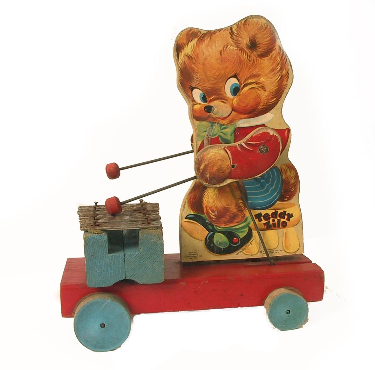 Lekebjørn som spiller xylofonLiten trevogn med 4 hjul,  malt rød og blå, på vognen  konturskåret figur av teddybjørn, som når vognen trekkes, spiller xylofon.  Tre, papir, metall    Figuren pålimt fargetrykk, glanset papir, m. tekst  Teddy Zilo./ Fisher Price Toys, Inc. East Aurora, N. Y.