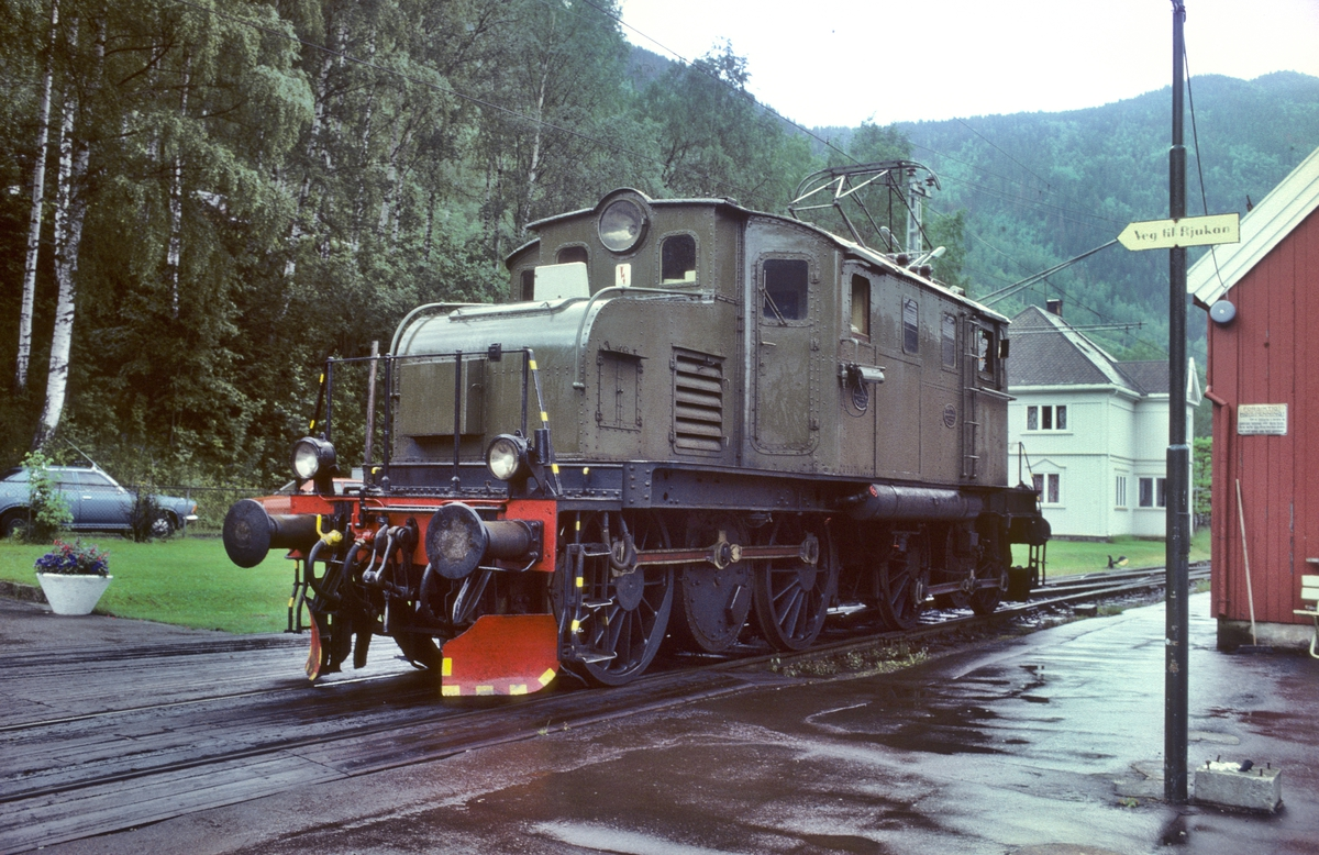 Rjukanbanens elektriske lokomotiv RjB 14 på Mæl stasjon. Skilt viser vegen for reisende til Rjukan. Norsk Hydro, Norsk Transportaktieselskap, Norsk Transport.