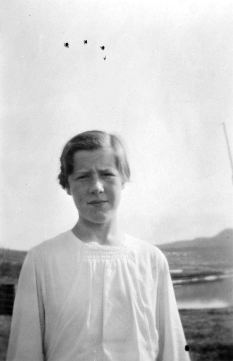 En ung pike i lys bluse tatt ute.