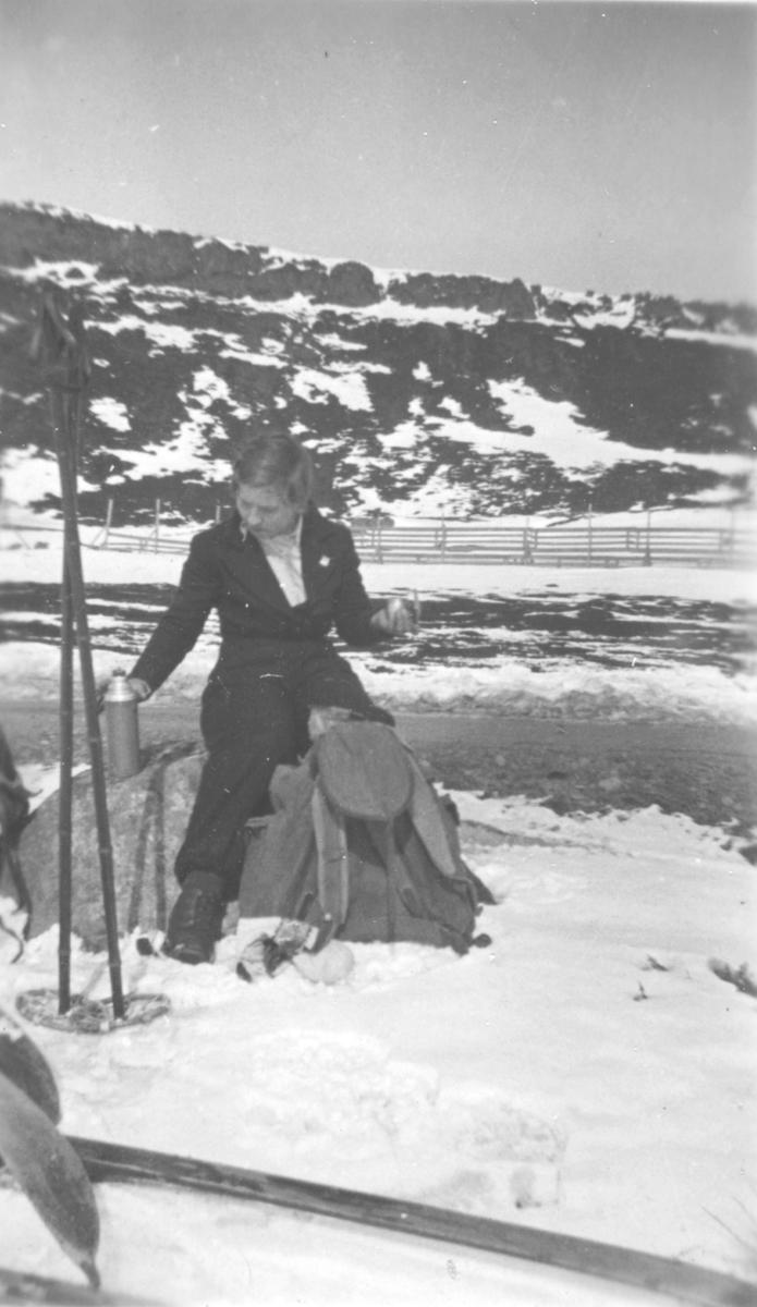 En dame sitter på en stein med en kaffeflaske i venstre hånd og en ryggsekk foran seg. Et par skistaver står i snøen.