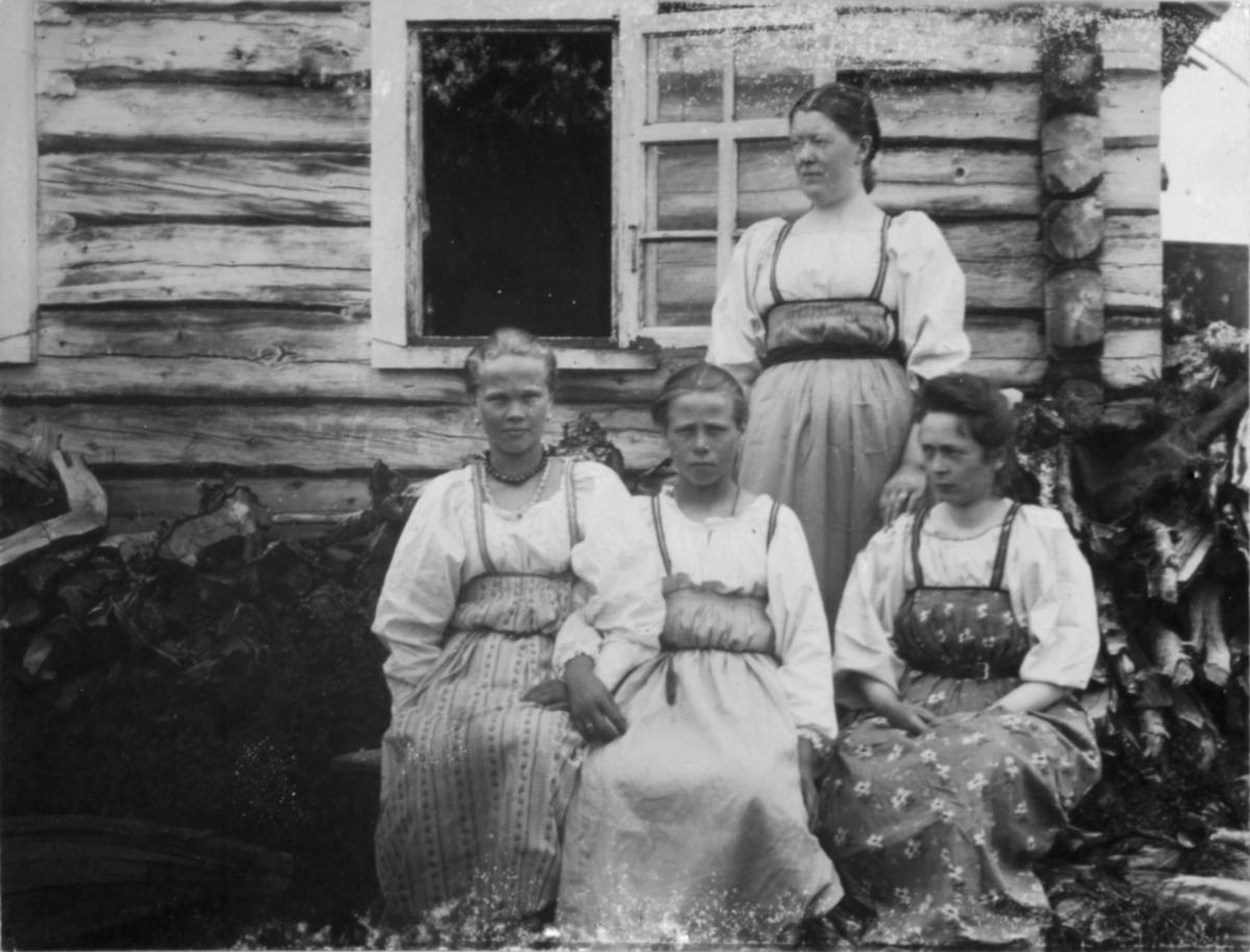 Fire damer foran en bygning. Tre av de sitter, og den ene står bak ved et åpent vindu. Foran huset er det stabler med ved. Damene har lyse bluser og side lyse skjørt med snøring i livet.