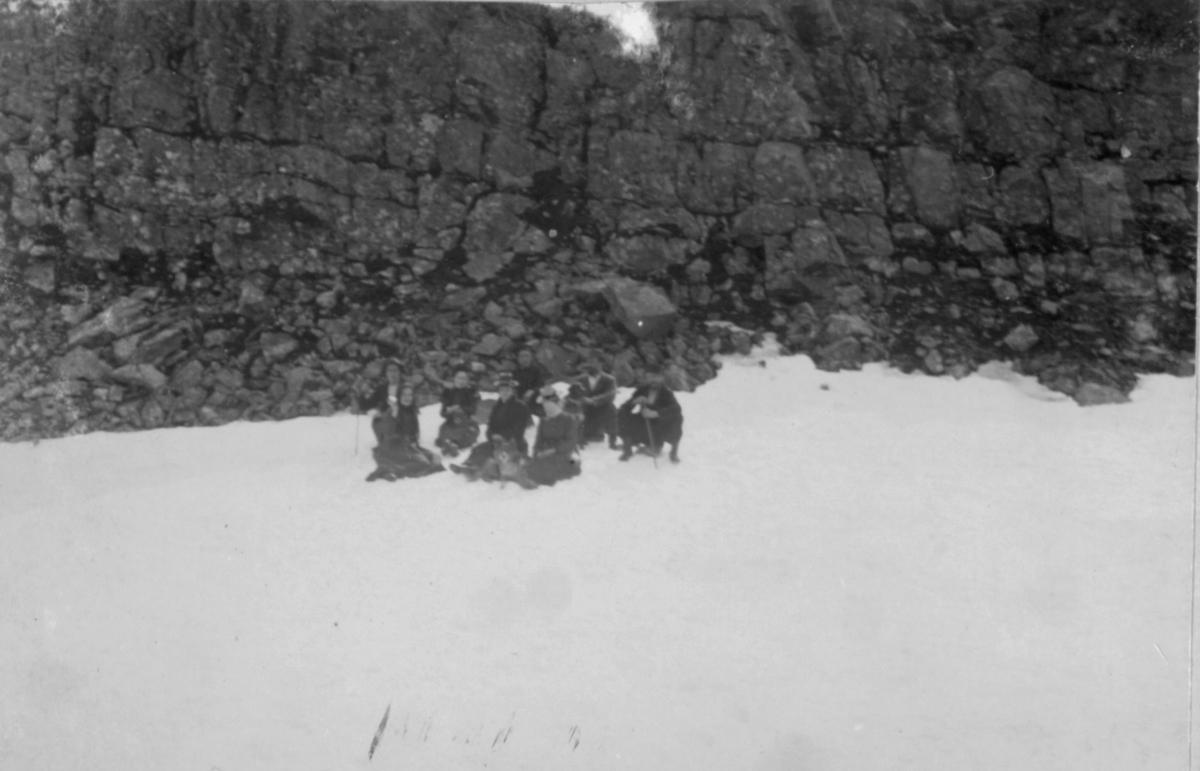 Damer og menn sitter i snøen ved en steinur.