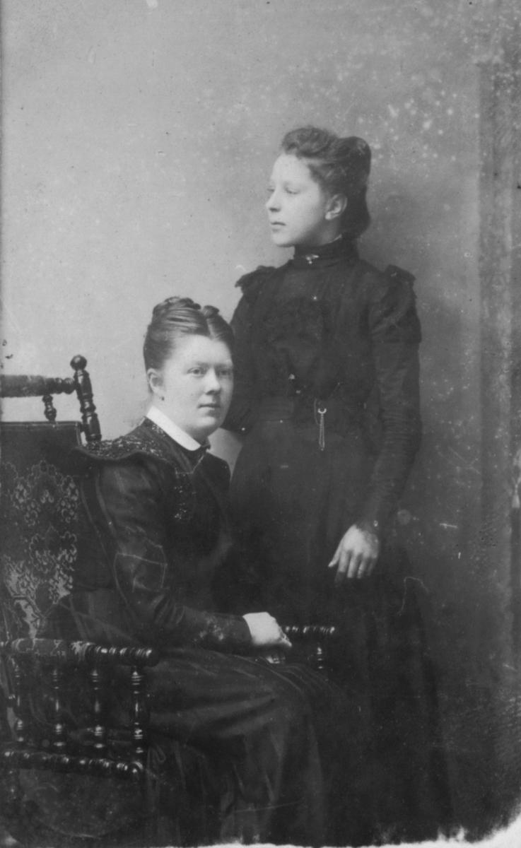 Karoline Ohlsen sitter på en stol. Ved siden av står en ung dame, antagelig søsteren hennes.