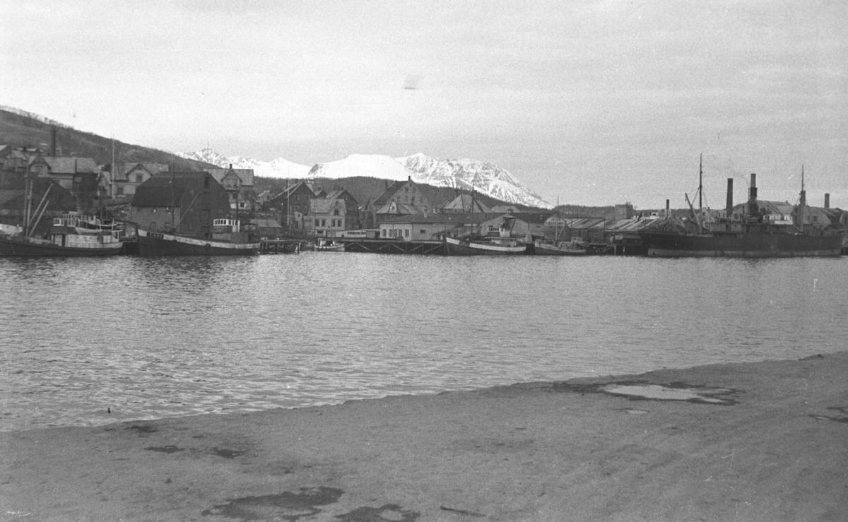 Et havneområde med flere båter langs kaiene. Stedet er ukjent, men kan være Harstad.