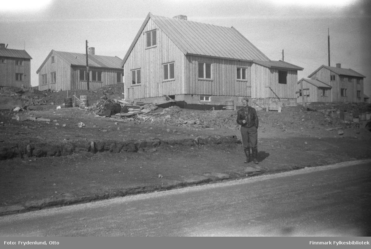 Mann foran gjenreisningshus i Oscarsgate i Vadsø. Huset nærmest kamera tilhørte familien Niemelæ. I følge bildeteksten tilhører de andre husene Kjeldsen og R. Johansen; disse husene må ha adresse Kirkegata