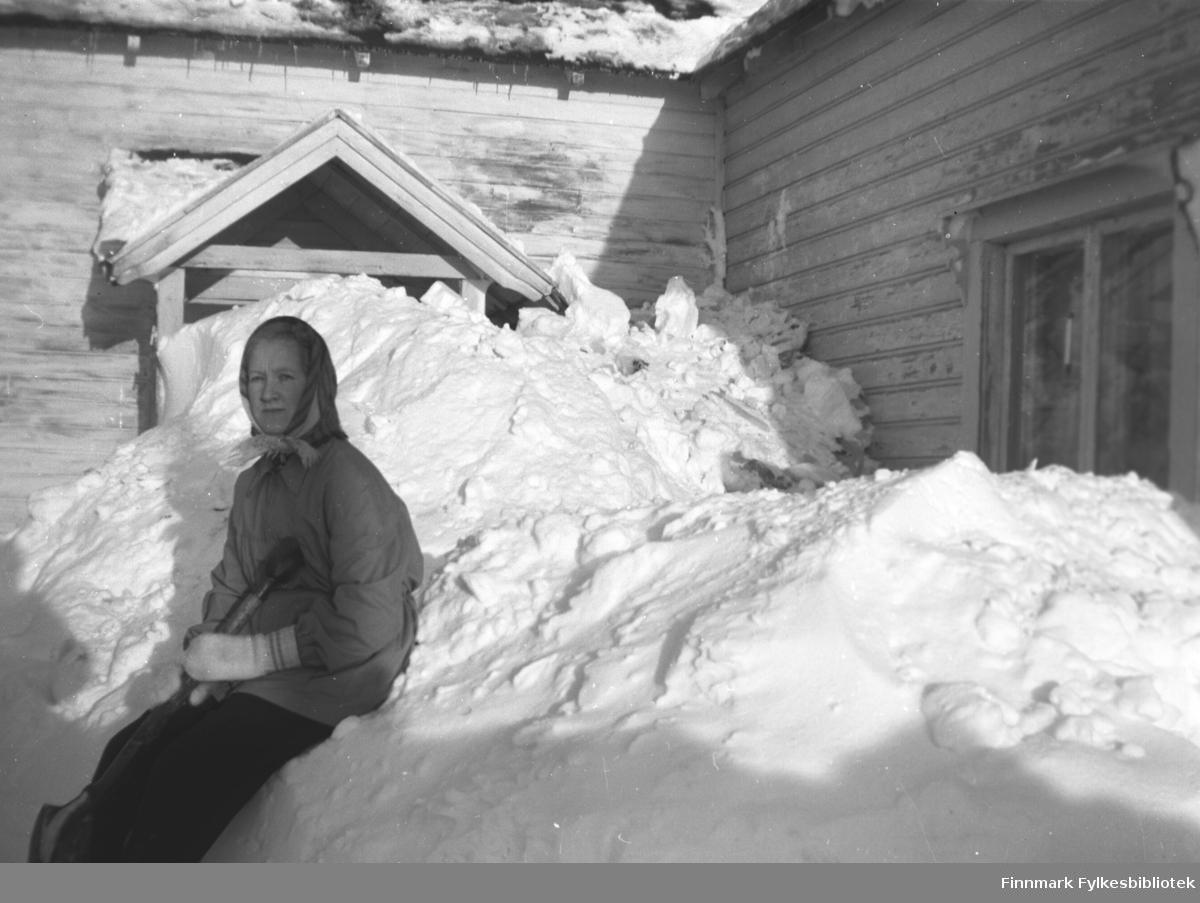 Herlaug Mikkola sitter i snøen utenfor hovedhuset på gården Mikkelsnes, ca. 1952. Dette må ha vært en skikkelig snøvinter!