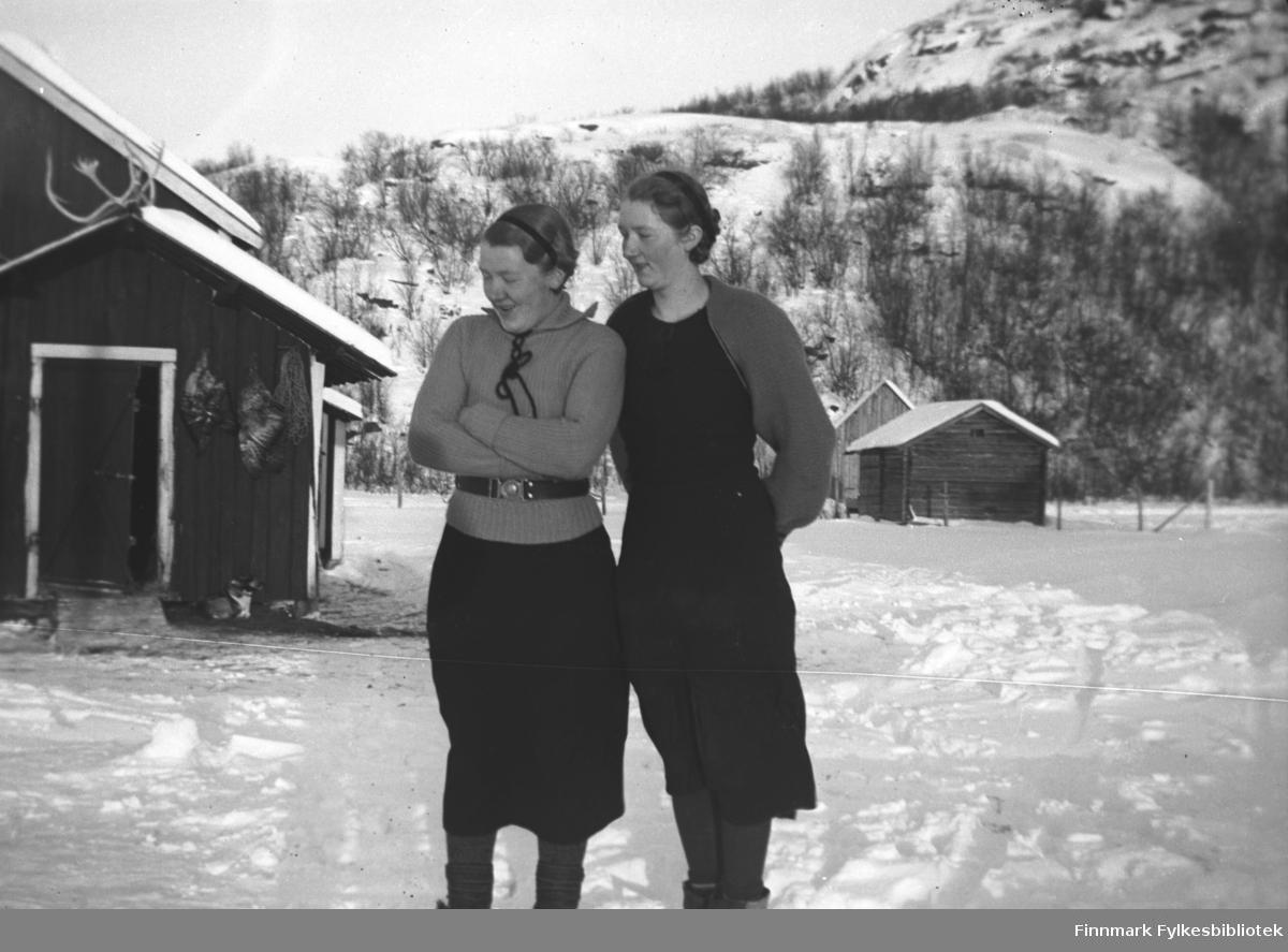 Søstrene Synnøve (til venstre) og Marine Mikkola på gårdsplassen foran gården Mikkelsnes. I bakgrunnen til høyre i bildet ser vi Haaheims lager og bak det Storm Mikkolas lastebilgarasje. På veggen på bygningen til venstre henger storfugl til mørning