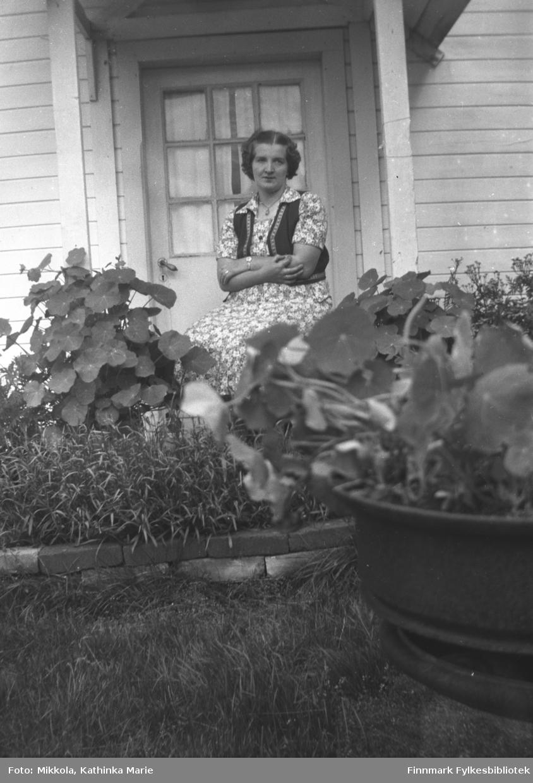 Astrid Lindseth sitter ved inngangsdøra til gården Mikkelsnes. I forgrunnen ser vi frodige hageblomster, bl.a. er blomkarsen lett å kjenne igjen